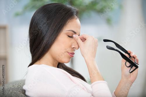 Fototapeta woman holding eyeglasses and rubbing the bridge of her nose obraz