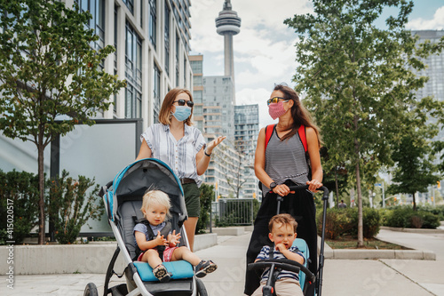 Fototapeta premium Two mothers walking down the street with kids in strollers. Friends in face masks chatting talking. People keeping the social physical distance outdoors during covid-19 coronavirus. New normal.