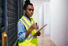 African American Woman In Datacenter Surveying Warehouse Is Secure