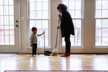Grandson Helping Grandmother Sweeping And Cleaning Floors At Home