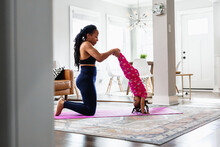 Mother Helps Daughter Do Yoga Handstand Exercise