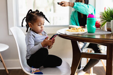 Toddler Watches Television Show On Phone At Dining Room Table