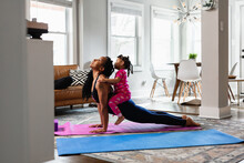 Mother And Daughter Working Out At Home Doing Exercises, Yoga Upward Facing Dog