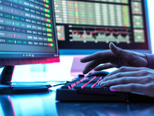 Hands Of Trader Typing On Keyboard In Front Of Computer Monitor Displaying Stock Market Data