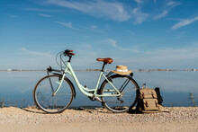Bicycle Parked With Backpack Leaning On Rear Wheel With Hat On Sunny Day At Ebro's Delta. Spain