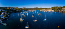 Spain, Mallorca, Andratx, Helicopter View Of Boats Sailing Near Shore Of Coastal Town At Summer Dusk