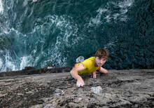 Passionate Young Male Rock Climber Climbing Rocky Cliff By Sea