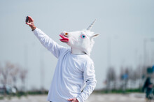 Man Wearing Unicorn Mask Taking A Photo With Smartphone