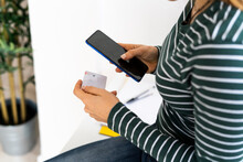 Female Professional With Credit Card Doing Online Shopping Through Smart Phone At Work Place