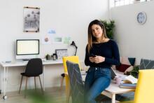 Smiling Female Freelancer Holding Mobile Phone Sitting On Table In Living Room