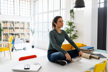 Creative Businesswoman Contemplating While Sitting On Tablet In Office