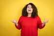 Young african american woman wearing red sweater over yellow background crazy and mad shouting and yelling with aggressive expression and arms raised. Frustration concept.