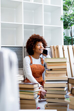 Afro Woman On Phone Call Surrounded By Stack Of Books While Moving In New Apartment