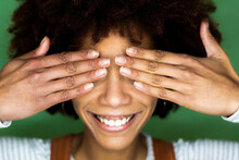 Happy Young Woman Covering Eyes With Hand Against Green Wall In New Home