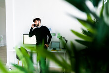 Businessman Talking On Smart Phone In Office, Green Plant Leaves In Foreground