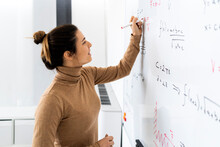 Smiling Young Woman Solving Mathematical Formula On Whiteboard At Home