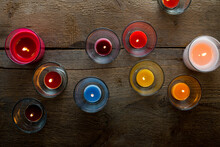 Colorful Glass Candles Burning On Wooden Surface