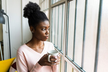 Woman With Coffee Cup Looking Through Window While Standing At Home
