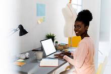 Smiling Fashion Designer Using Laptop While Sitting At Home Office