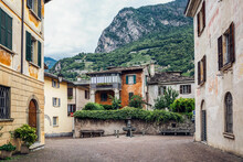Road Amidst Buildings In Old Town Against Mountain, Valchiavenna, Chiavenna, Province Of Sondrio, Lombardy, Italy