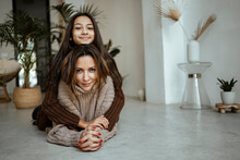 Smiling Daughter With Arms Around Of Mother While Lying On Floor At Home