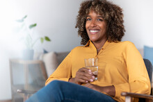 Smiling Woman Drinking Water While Sitting At Home