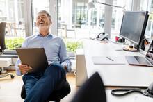 Smiling Entrepreneur Using Digital Tablet While Sitting At Office