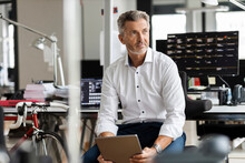 Mature Businessman With Digital Tablet Looking Away While Sitting At Office