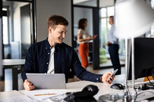 Young Businessman Using Mobile Phone While Sitting With Colleague In Background At Open Plan Office