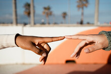 Close-up Of Friends Index Finger Pointing Each Other Outdoors