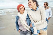 Group Of Friends Walking Together Along Sandy Coastal Beach