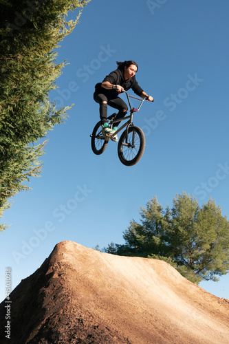 Foto Caucasian white with long hair boy jumping with BMX bike on a mountain in the fi