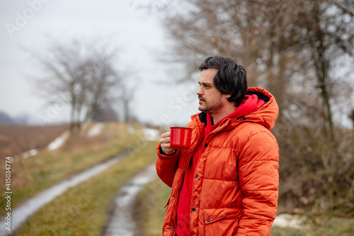 Hipster guy with red mug drink a coffee in countryside © Masson