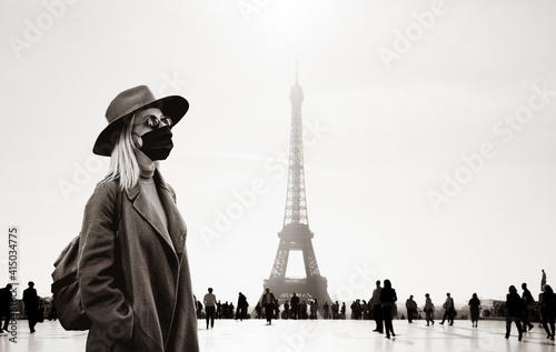 Style woman in face mask and sunglasses with Eiffel tower on background © Masson