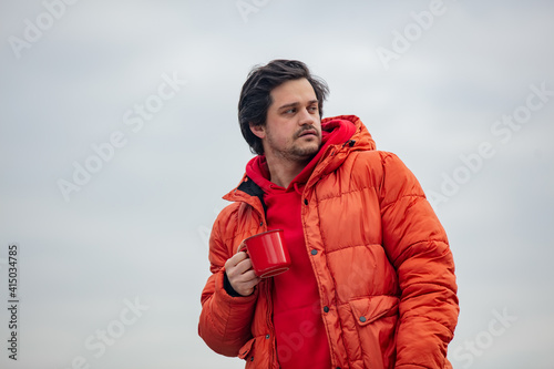 Hipster guy with red mug drink a coffee in outdoor with clouds on background © Masson
