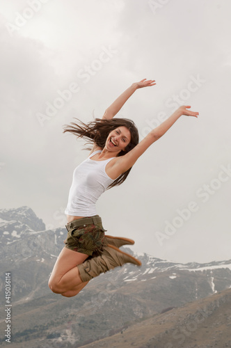 Giovane donna salta felice con le braccia in alto Fototapet