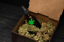 Glass Bottle Of Cannabis Cbd Oil. Box With Cbd Oil And Cannabis Buds. Bottle With Green Marijuana Leaf On It. Essential Medical Cannabis Oil.