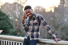 Modern Black African American Man Wearing Stylish Clothes And Earring Speaking On Smartphone While Standing On Metal Bridge Fence On The Street
