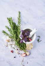 From Above Pestle And Mortar With Blossoming Flowers Near Garlic Cloves And Fresh Rosemary On Marble Table