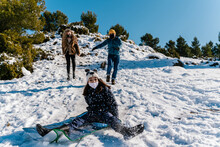 Cheerful Teenager Riding Snowy Slope In Winter On Background Of Carefree Parents Having Fun Together In Woods At Weekend