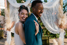 Side View Of Delighted Bride Hugging Cheerful Black Groom From Behind While Enjoying Wedding Day Together In Summer Garden