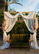 Soft Sofa Placed Under Wooden Wedding Arch Decorated With Tulle Curtains And Dry Pampas Grass And Placed In Park At Sunset