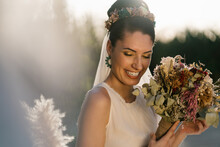 Charming Bride In White Dress And With Bridal Bouquet Of Flowers Smiling On Wedding Day In Summer Garden