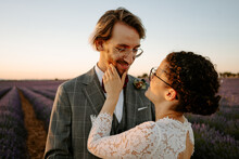 Content Bride In White Dress Touching Face Of Smiling Groom In Suit While Standing In Lavender Field At Sunset And Looking At Camera