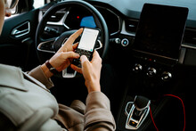 Crop Unrecognizable Male Entrepreneur Sitting On Driver Seat In Luxury Automobile And Browsing Mobile Phone