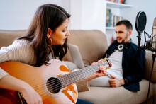 Couple Of Musicians Sitting On Sofa And Recording Song While Playing Acoustic Guitar And Using Laptop