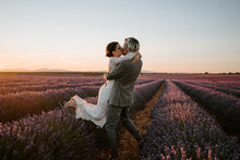 Side View Of Groom Lifting Bride While Standing In Lavender Field On Background Of Sunset Sky On Wedding Day