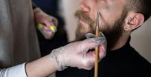 Close-up Of An Unrecognizable Makeup Artist Putting Makeup On A Hipster Man's Face