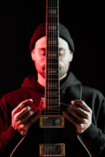 Tranquil Male Rock Musician Standing With Electric Guitar On Black Background In Studio With Red Light