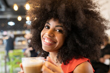 Content African American Charming Female With Afro Hairstyle And Cup Of Cappuccino Looking At Camera While Enjoying Weekend In Cafe